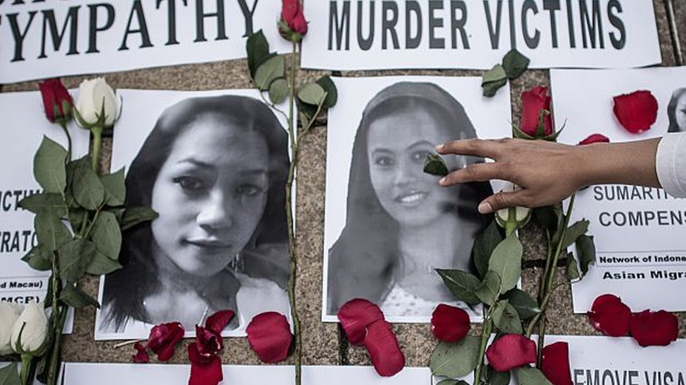 An Indonesian migrant worker lays rose petals over the pictures of murder victims in Hong Kong on 9 November 2014.