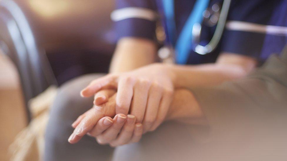 Una enfermera sostiene la mano de un paciente