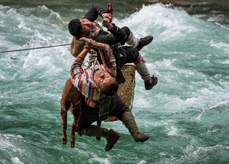 Dvojica muškaraca i životinja se prevoze žičarom iznad nabujale reke