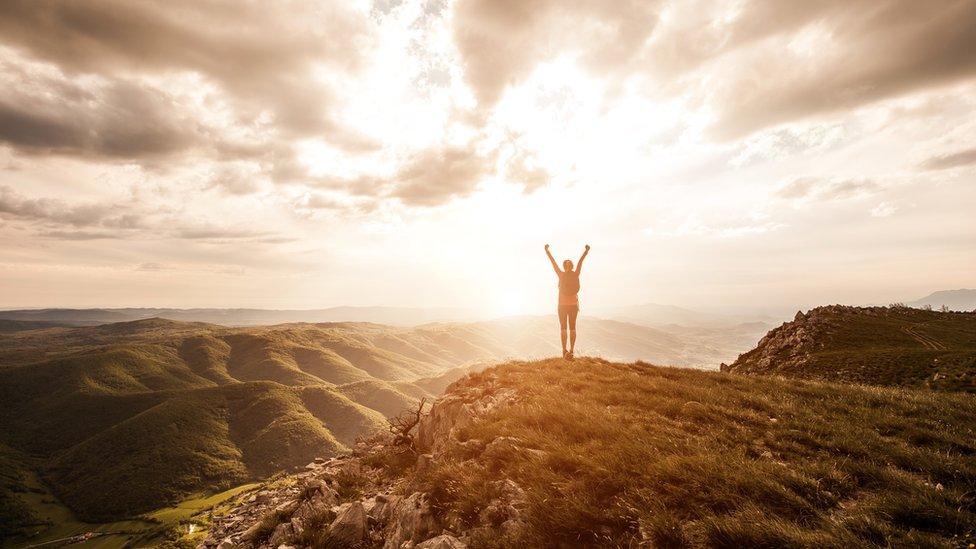 Mujer en lo alto de una montaña al amanecer