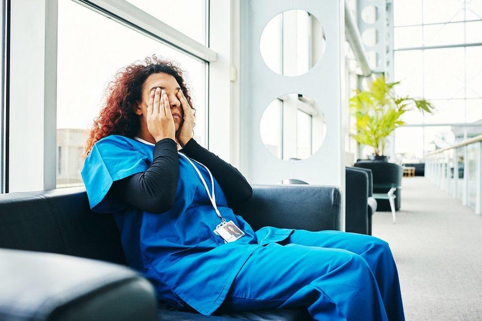 Una enfermera sentada en un sofá tocándose los ojos por el