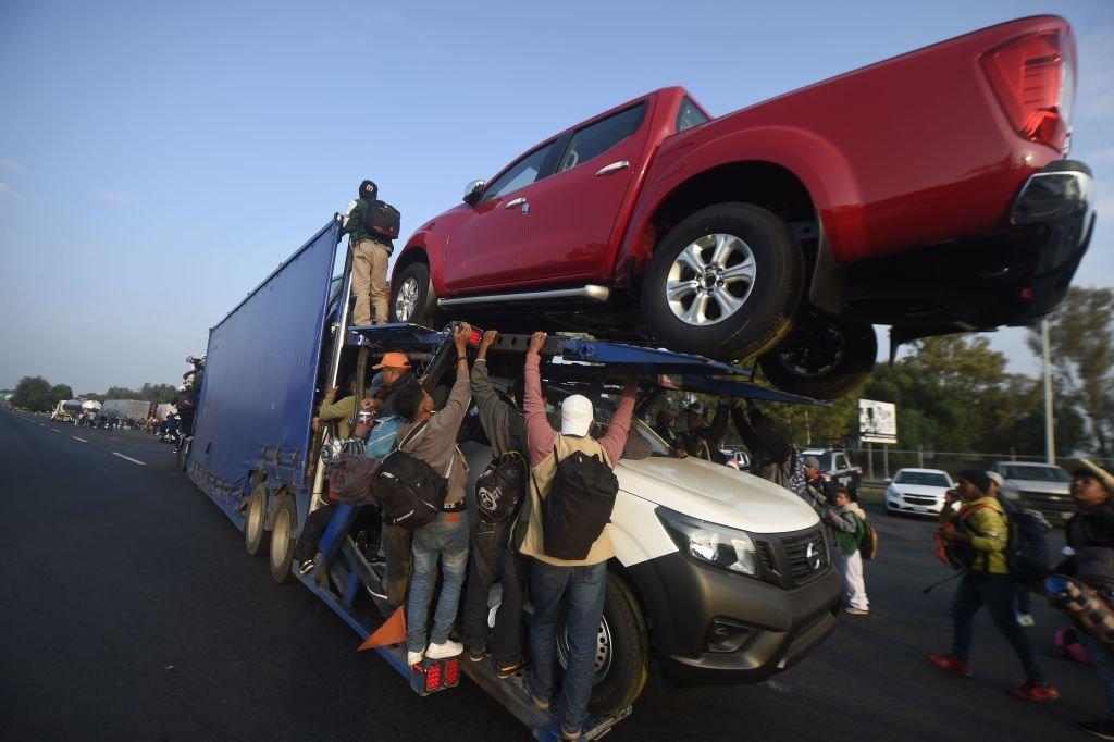 Migrantes trepan a un tráiler con autos nuevos