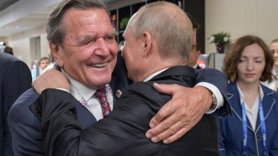 غيرهارد شرودر (اليسار) يعانق الرئيس الروسي بوتين أثناء افتتاح كأس العالم لكرة القدم في موسكو عام 2018