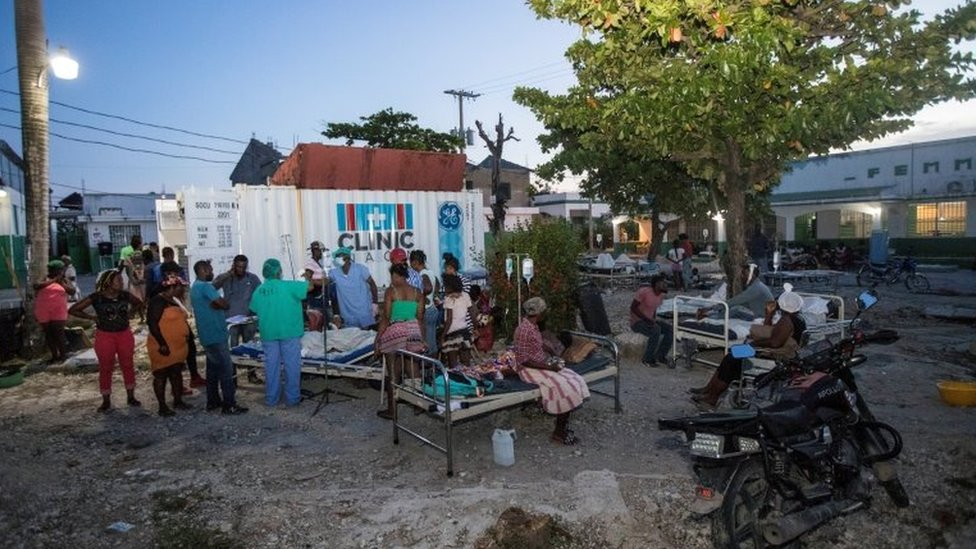 Patients accompanied by their relatives are seen outside a hospital damaged following a 7.2 magnitude earthquake in Les Cayes,