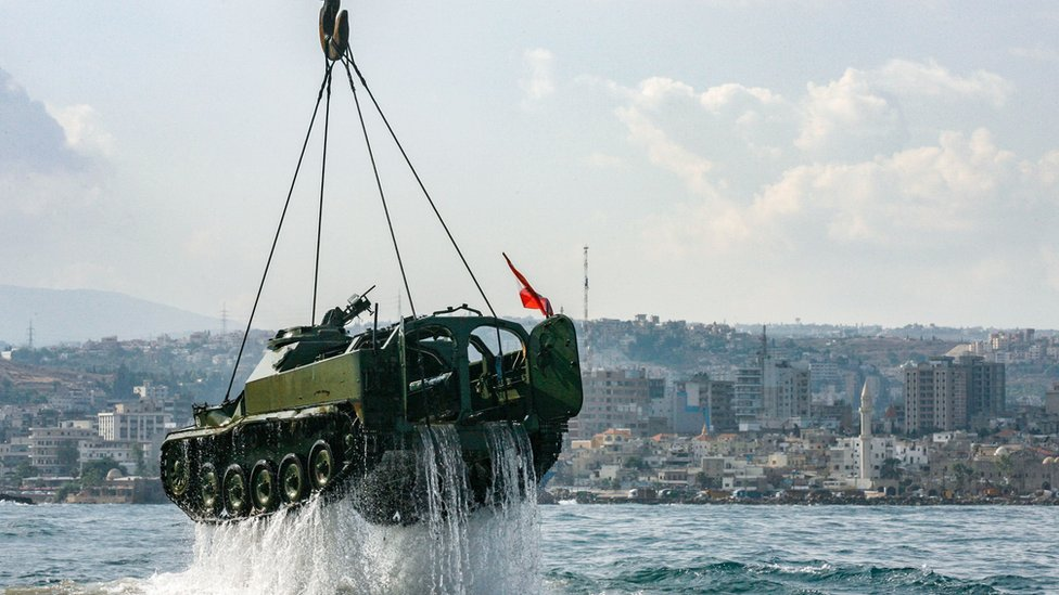 Environmental activists drop off old battle tanks provided by the Lebanese Armed Forces into the Mediterranean Sea