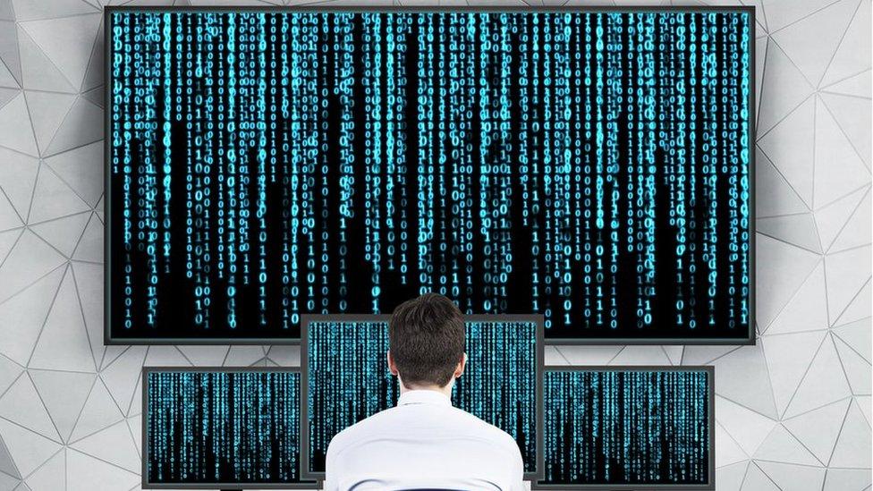 Man looking at matrix on computers