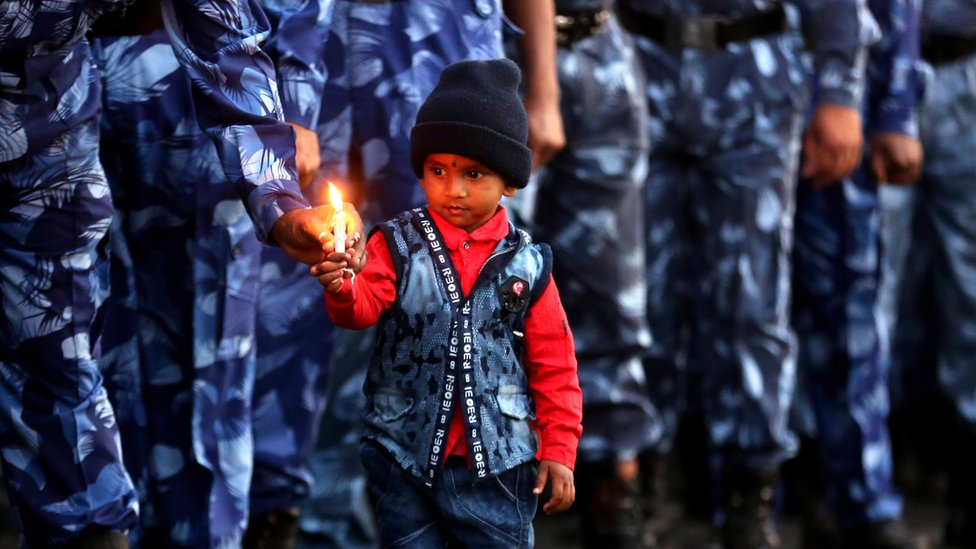 Rapid Action Force soldiers and a child from one of their families hold candles as they pay tribute to personnel during a candlelight vigil in Bhopal