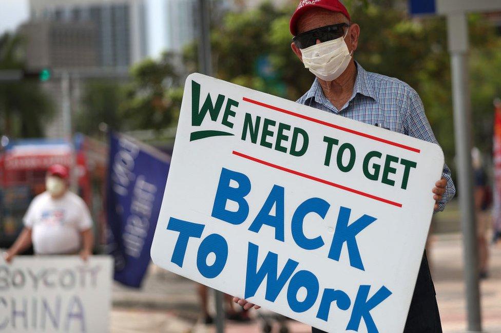 Hombre con cartel pidiendo la vuelta al trabajo.