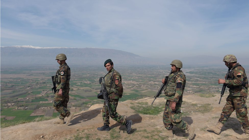 Afghan National Army (ANA) soldiers walk through Dand-e-Ghori district in Baghlan province