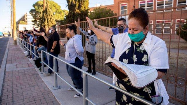 Personas con los brazos en alto rezan a las puertas del Centro Méidco de la Universidad de El Paso.