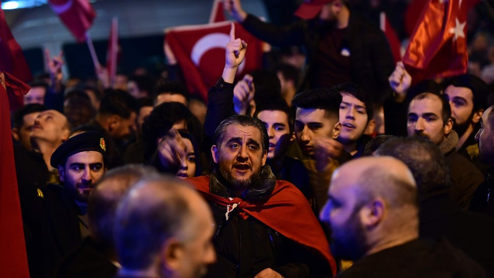 People gesture and wave flags as Turkish residents of the Netherlands gather for a protest outside Turkey's consulate in Rotterdam on March 11, 2017