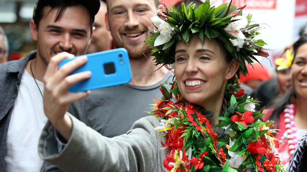 """New Zealand""""s Prime Minister Jacinda Ardern takes pictures with supporters during a campaign outing at Mangere Town Centre and market in Auckland, New Zealand, October 10, 2020."""
