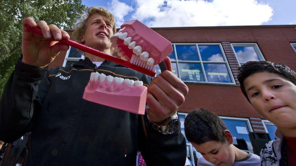 Profesor enseñando a cepillarse los dientes