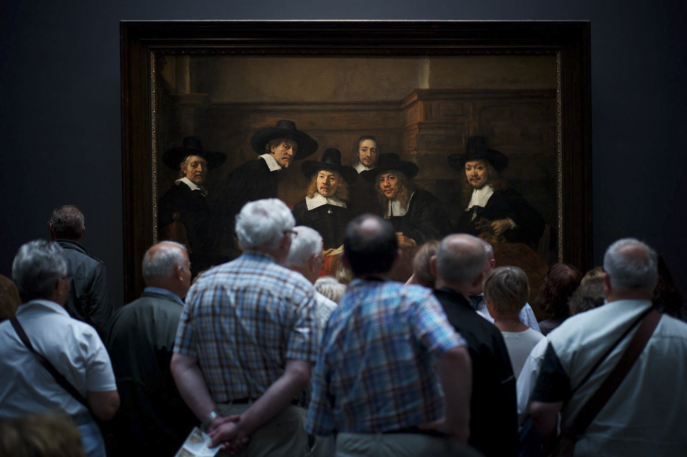 Museum visitors watching Rembrandt's painting Syndics of the Drapers' Guild