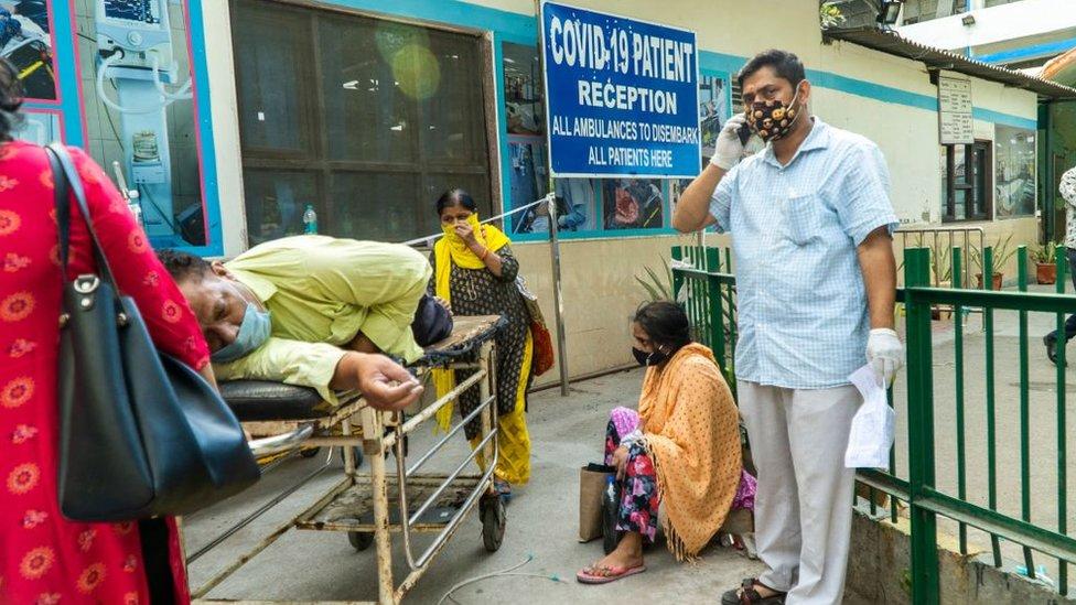 Nesta foto tirada em 23 de abril de 2021, parentes esperam ao lado de um paciente com coronavírus deitado em uma maca em um complexo hospitalar para internação em Nova Delhi