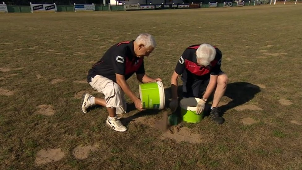 Groundsmen filling holes