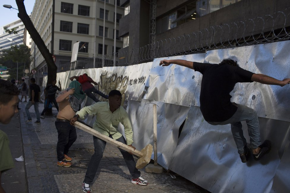 Anti-austerity demonstrators kick down the fence of a building, closed for construction, to build a road block near the state legislature where lawmakers are discussing austerity measures in Rio de Janeiro, Brazil, Tuesday, 6 December