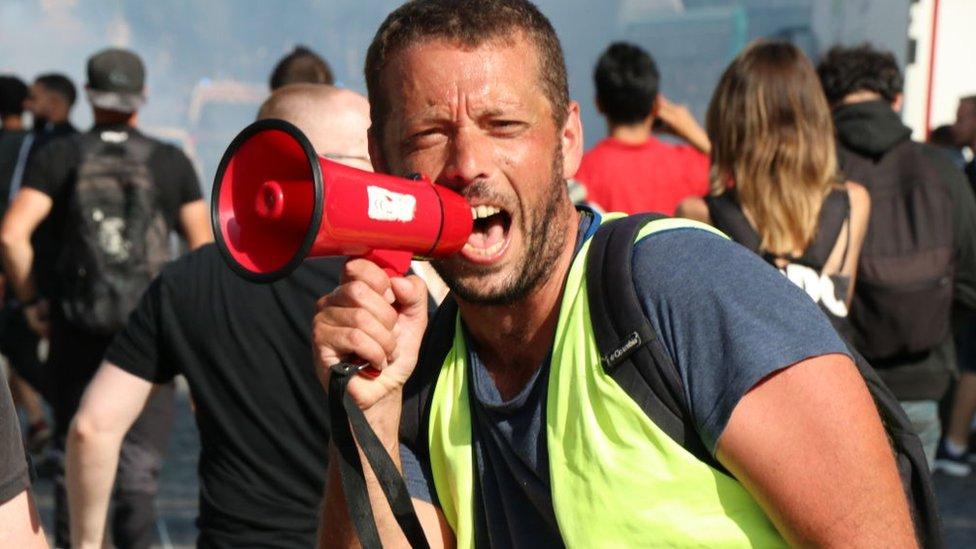 متظاهر يصرخ عبر مكبر صوت