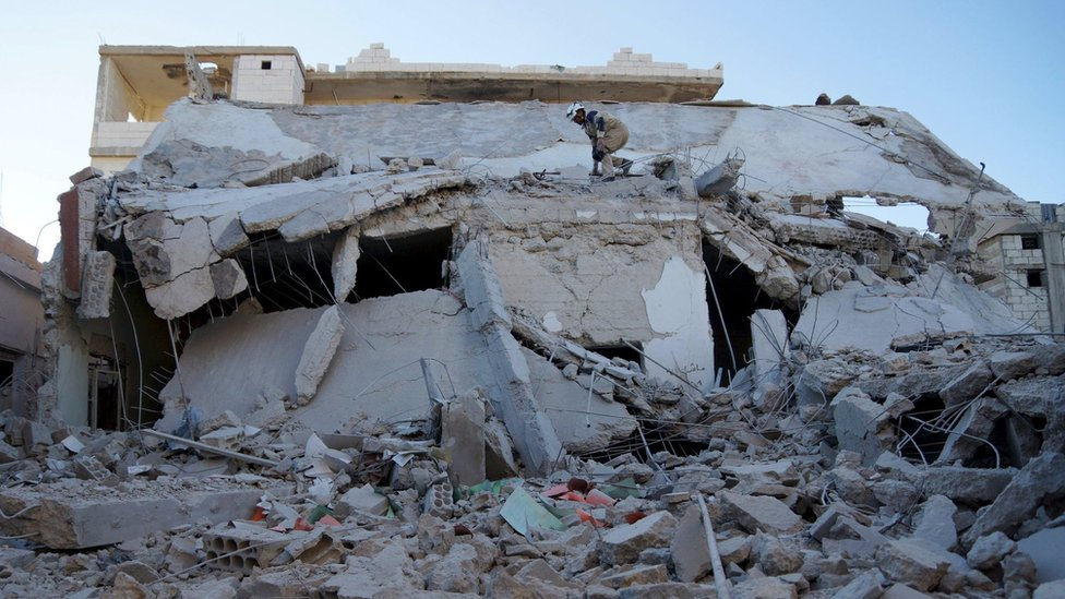 Civil defence members inspect a site attacked by what activists said were Russian aircraft in Sheikh Miskeen, Syria (24 December 2015)