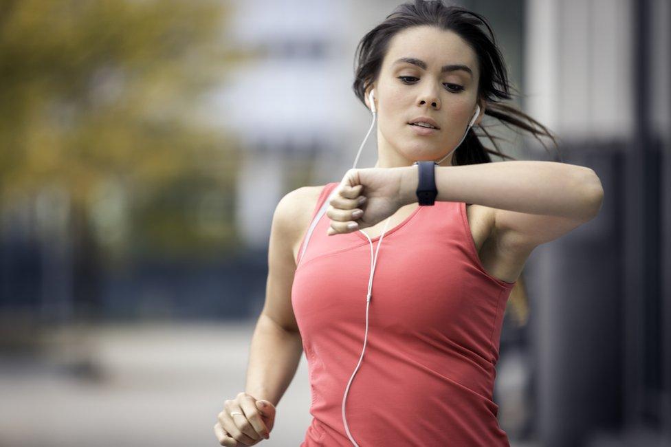 Žena džogira i gleda u uređaj za fitnes podatke na ruci