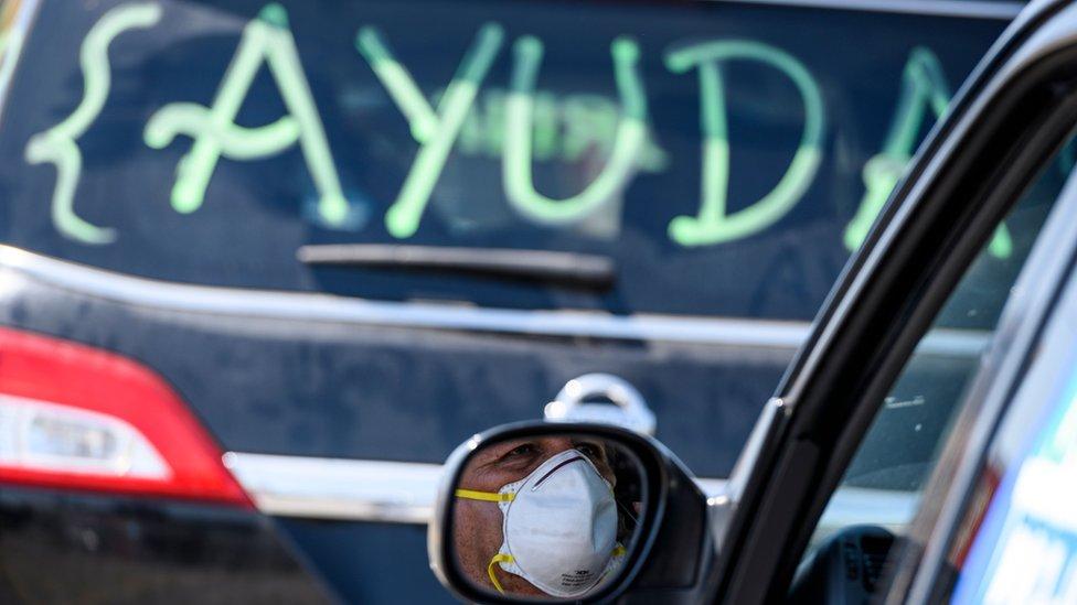 """Dos autos, uno de ellos con un cartel que dice """"Ayuda"""""""