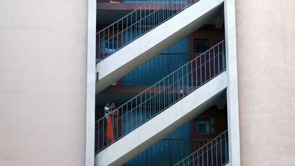 """A woman and a child stand in a stairwell at """"Les Rosiers"""" neighbourhood in Marseille"""