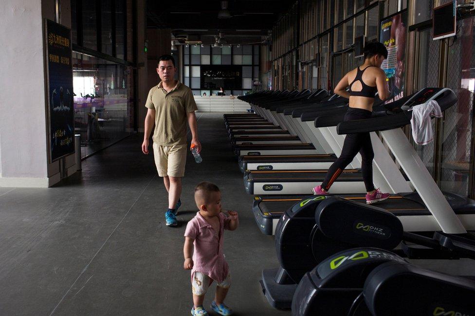 Muž Deng Peipeng se brine o sonu dok Huang trenira u lokalnoj teretani u gradu Lijangđijang.