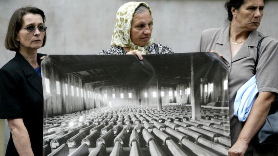 Survivors and relatives of victims of the Srebrenica massacre hold a picture of coffins at a protest in 2004