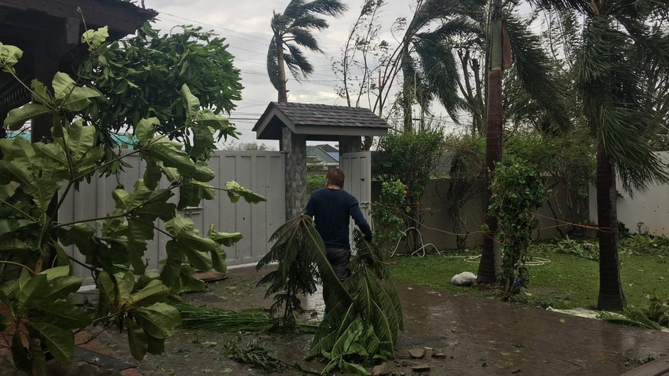 Carmelo Lasam clears up his garden the morning after Typhoon Mangkhut