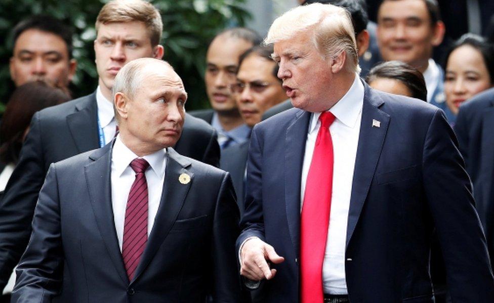 Russia's President Vladimir Putin walks alongside US President Donald Trump in November 2017