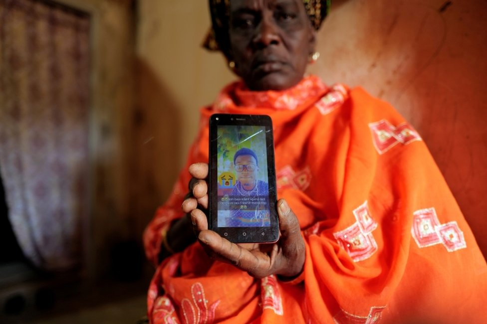 A distraught woman holds up a mobile phone with a photo of her late son on the screen.
