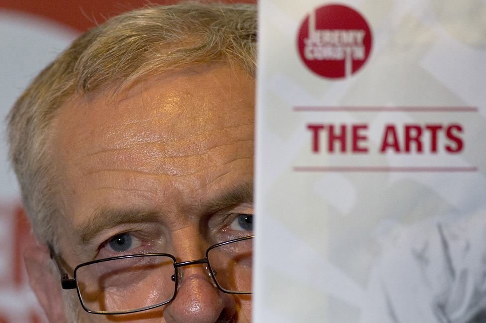 Jeremy Corbyn peers around a leaflet entitled The Arts