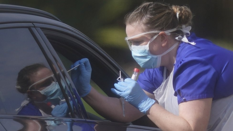 A medical worker swabs a motorist at a testing centre