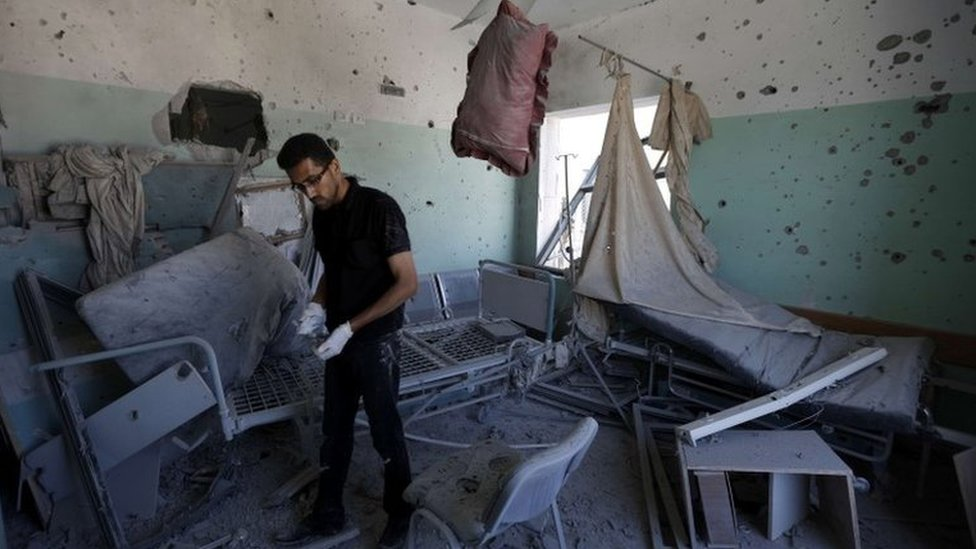 A Palestinian employee inspects damages at the al-Aqsa hospital in Deir al-Balah