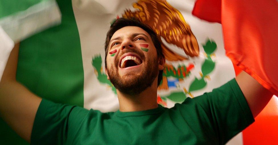 Mexicano con bandera celebrando.