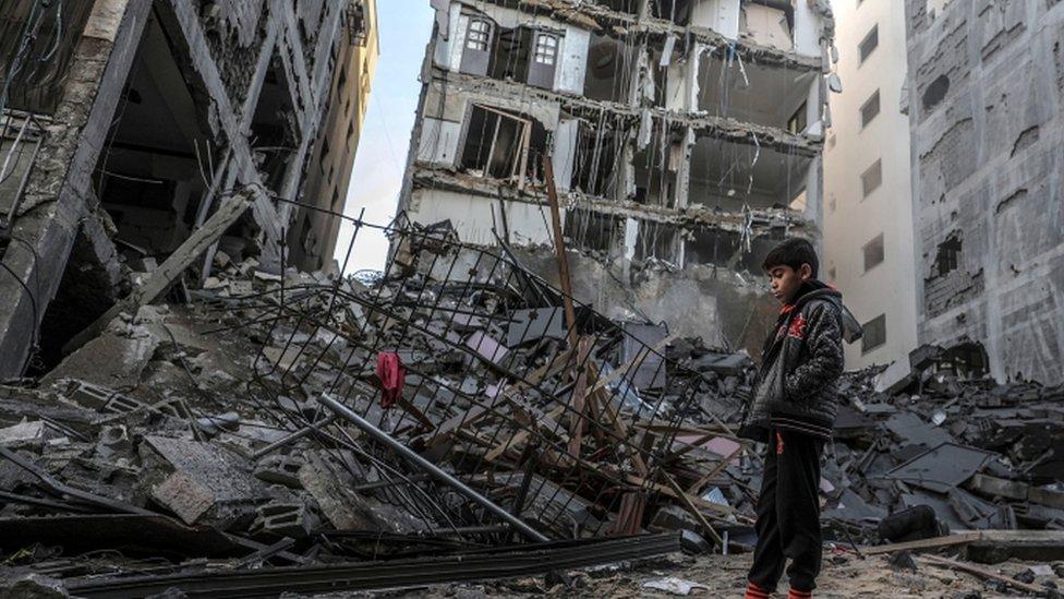 طفل فلسطيني يقف على أنقاض مبنى دمره القصف الإسرائيلي لغزة
