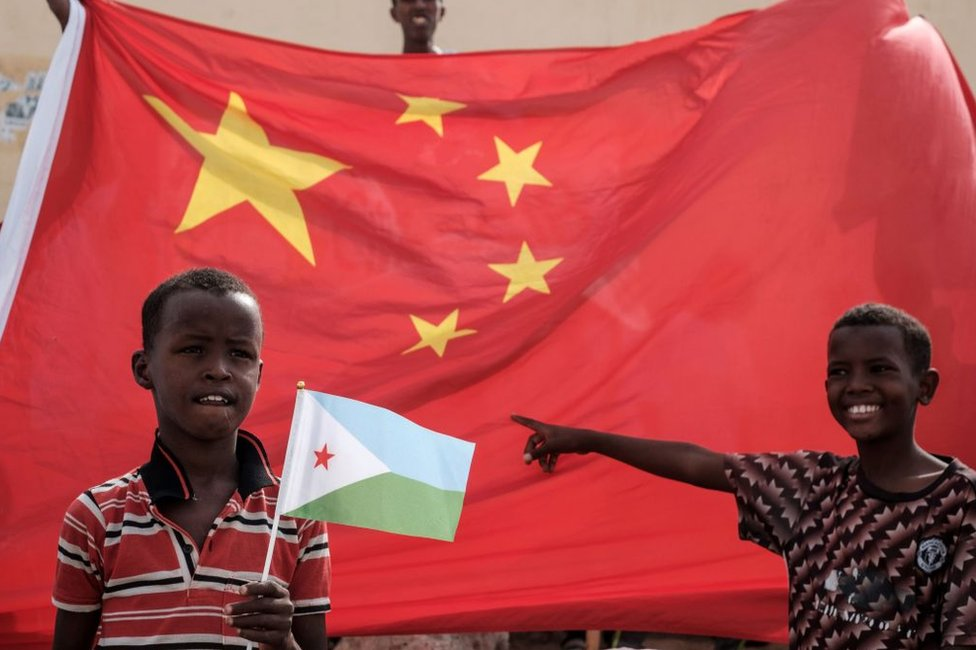 A boy holds Djiboutian national flag in front of Chinese national flag as he waits for Djibouti's President Ismail Omar Guellehas before the launching ceremony of new 1000-unit housing construction project in Djibouti, on July 4, 2018. - The new 1000-unit construction project by the Ismail Omar Guelleh Foundation for Housing is financially supported by China Merchant, the operation parther of newly inaugurated Djibouti International Free Trade Zone (DITTZ) with Djibouti Ports and Free Zones Authority, to build basic two bedroom apartments for low income people.