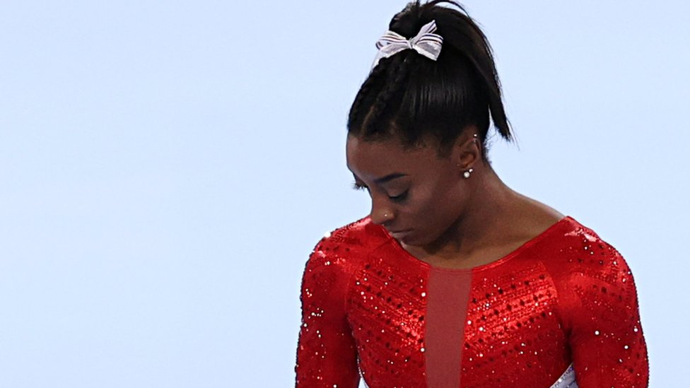 Simone Biles looks down in disappointment