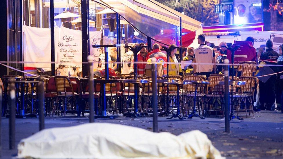 Una víctima cubierta frente a un café parisino.
