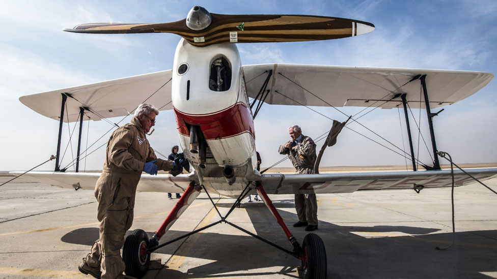 A German pilot checks his Bu 131 Bucker Jungmann biplane after landing at an airfield in Cairo, Egypt during the Vintage Air Rally (VAR) on November 13, 2016.