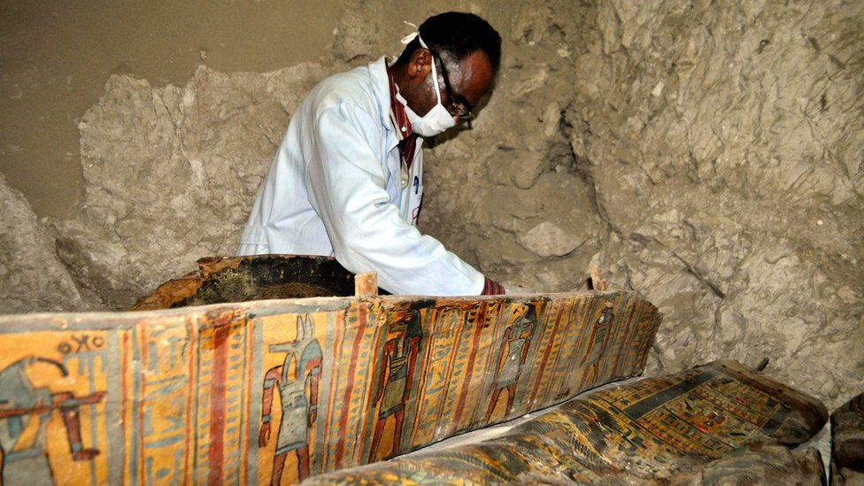 An archaeologist in a mask working on a colourfully-painted coffin inside a tomb