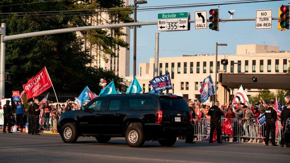 Un auto del convoy presidencial pasa frente a simpatizantes del presidente frente al hospital Walter Reed.