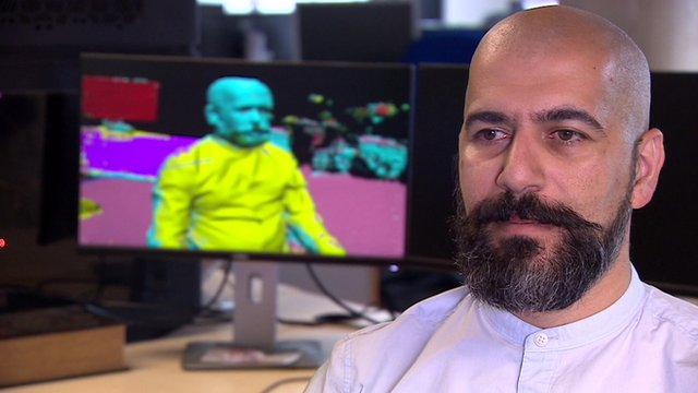 A man sitting next to a computer rendered image of himself