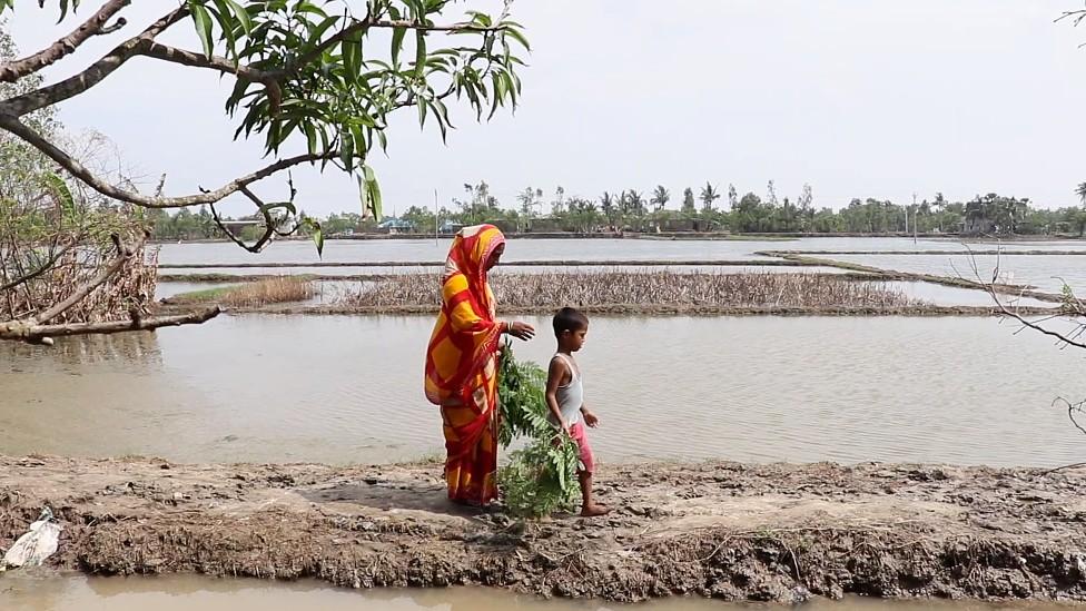 Feroza camina con su hijo de 6 años en un corrredor de tierra angosto rodeado por agua