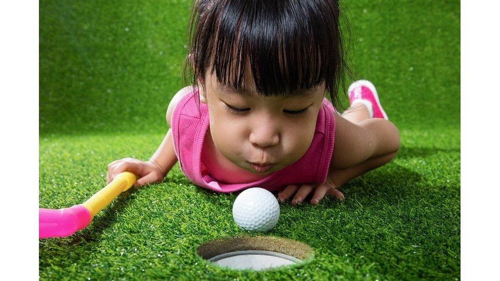 فتاة صغيرة تلعب بكرة