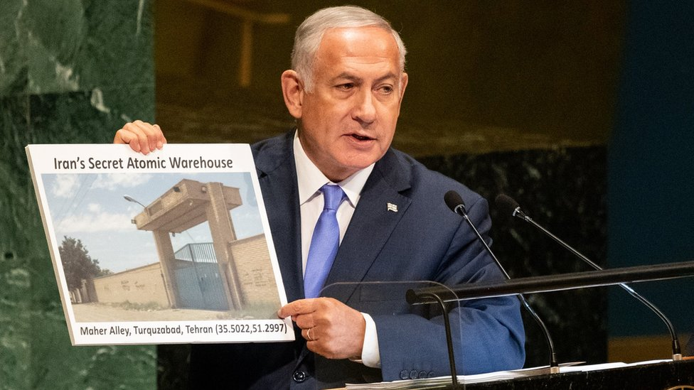 """Benjamin Netanyahu holds a picture of what he described as """"Iran's secret atomic warehouse"""" in Tehran's Turquzabad district (27/09/18)"""