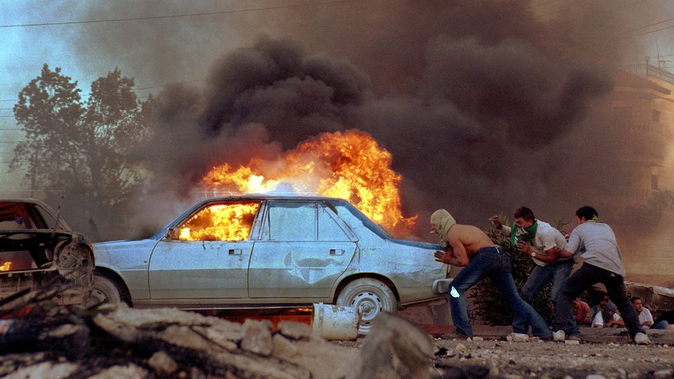 Palestinians burn cars as protests flared near the West Bank town of Ramallah, 2000
