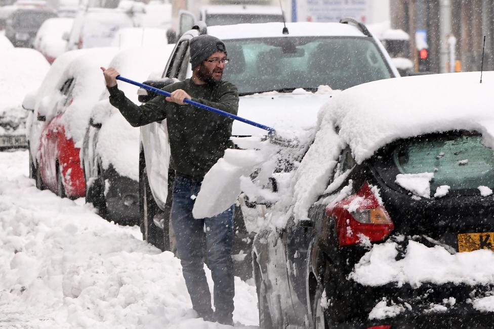 رجل يزيل الجليد من على سيارته في بلدة أوختيراردير في مقاطعة بيرث وكينروس في اسكتلندا.
