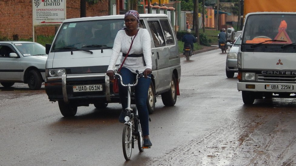 Amanda Ngabirano monta su bicicleta en una calle con tráfico.