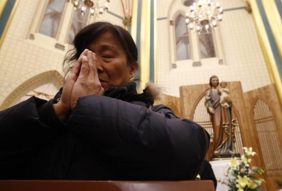 žena se moli u katedrali u Pekingu
